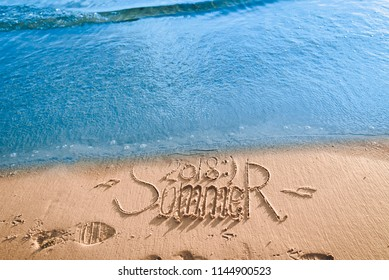 Summer passed the concept. The wave washes away the inscription summer 2018 written on the sand. End of vacation and season.