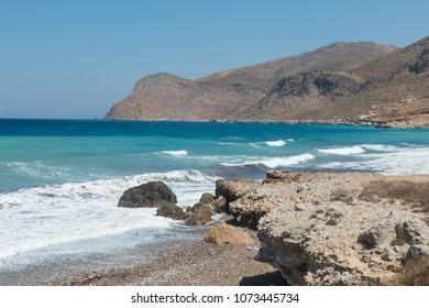 Summer. Pebble Beach. Clear Blue Sky, Surf, Waves of the Aegean Sea, Deserted Coast of Tilos Island. Dodecanese, Greece.