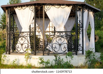 Summer pergola with decorative WrouGht iron  details, curtains And roof. Dining zone. Summerhouse.