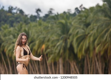 Summer Philippine vacation travel. Happy woman doing thumbs up approving gesture at exotic tropical beach with palm trees background. Palawan, Philippine.