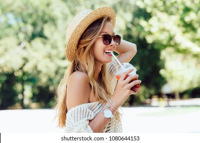 Summer photo of lovely cheerful woman in sunglasses, drinking a fresh cocktail from straw, while walking outside. Dressed in stylish clothes, in hat.
