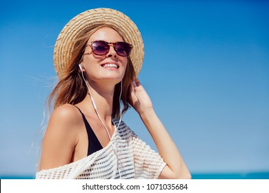 Summer photo of a pretty woman in sunglasses, listening to music in earphones, on smartphone, outdoors. Dressed in stylish clothes and hat.
