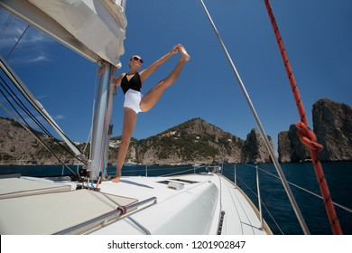 Summer photo of  woman in bikini practicing yoga and stretching her leg on a sailing yacht floating on the sea against the background of cliffs and beach, during summer vacation in Spain