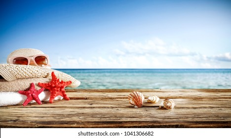 Summer photo of wooden desk and travel tools. Free space for your decoration. Blurred beach background.