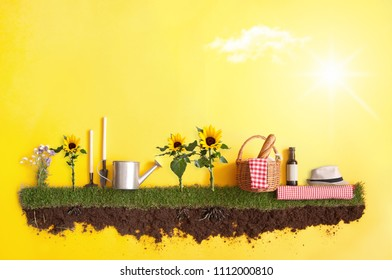 Summer picnic basket on grass patch with sunflowers
