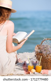 Summer - picnic by the sea. Girl in Hat read book and basket for a picnic with buns, apples and juice.