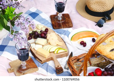 Summer picnic with cheese, wine, fruits and bread. Picnic at the park.