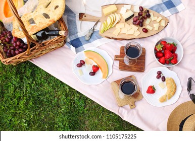 Summer picnic with cheese, wine, fruits and bread. Picnic at the park, flat lay, copy space.
