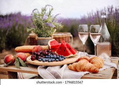 A summer picnic in a lavender field with watermelon, croissants and a bottle of rose wine and two glasses. Beautiful rustic decor. Gorizontal format.