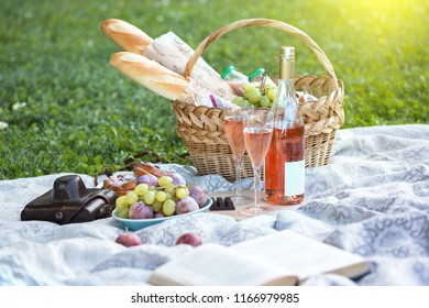 Summer - picnic in the meadow.  baguette, wine, glasses, grapes and rolls in a basket on green grass