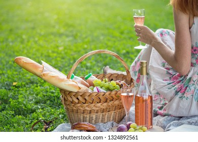 Summer - picnic in the meadow.  girl with a glass of wine and near a picnic basket and baguette, wine, glasses, grapes and rolls