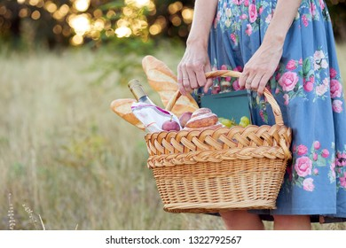Summer - picnic in the meadow.  girl holding a basket for a picnic with baguette, wine, glasses, grapes and rolls