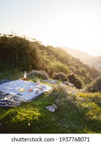 Summer picnic outdoors with blanket, eco style, plate of fruits, cheese, croissants and glasses of wine. Romantic picnic with seaside and mountain view at sunset