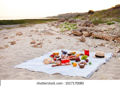 Summer Picnic: pizza and various fruits on the beach at sunset in the white plaid, food and drink conception.