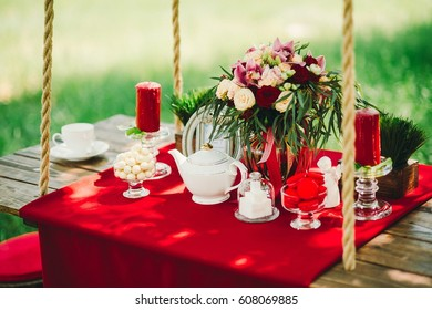 Summer picnic - table with a red tablecloth, around the green grass and trees, a bouquet of flowers on the table
