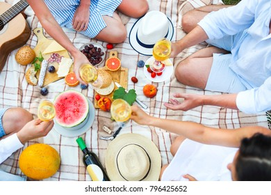 Summer picnic with white wine top view. Toasting people