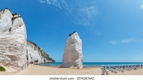 Summer picturesque Beach of Pizzomunno with famous white rock, in Vieste, Gargano coast, Puglia, Italy.  Two shots stitch panorama.