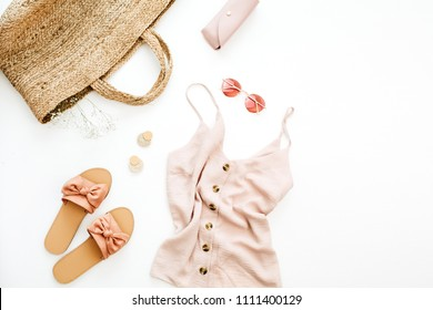 Summer pink feminine clothes and accessories on white background. Flat lay, top view. Summer fashion concept.