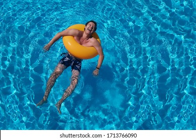 Summer pool with an orange circle and a laughing guy. Saturated blue water background. Summer holidays, laughter, joy of life and cheerful man.