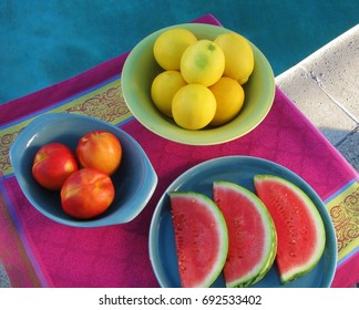 Summer poolside party table with lemons, nectarines and watermelon slices in retro, midcentury modern dinnerware on bright print tablecloth
