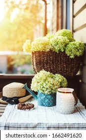 summer porch decoration with flowers and candles. Romantic evening at wooden cottage, gardening and country living concept.
