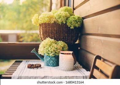 Sommerporkendekoration mit Blumen und Kerzen. Romantischer Abend in Holzhütte, Gartenarbeit und Landleben Konzept.