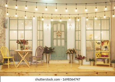 Summer porch with garlands of light bulbs. Terrace of summer house design of photo Studio. Patio verandah with flowers in metal buckets and wooden chairs and table. Street garland with light bulb - Shutterstock ID 1698364747