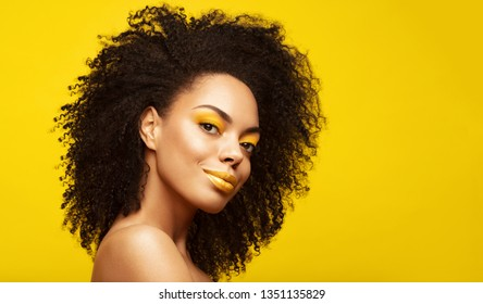 Summer portrait of African American Fashion Model  . Brunette young woman with afro hair style, creative yellow make up, lips and eyeshadows on colorful background. Summer beauty concept