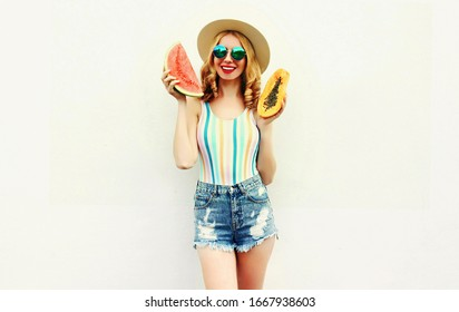 Summer portrait attractive smiling woman with slice of watermelon and papaya wearing straw hat, sunglasses, shorts over white background