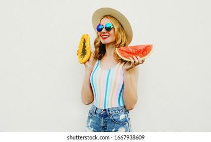 Sommerporträt attraktive Lächlerin mit einer Scheibe Wassermelone und Papaya mit Strohhut, Sonnenbrille, kurze Hosen auf weißem Hintergrund