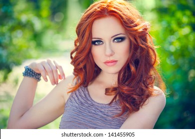 Summer portrait of a beautiful girl with long curly red hair