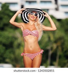 Summer portrait of beautiful slim woman in hat and bikini