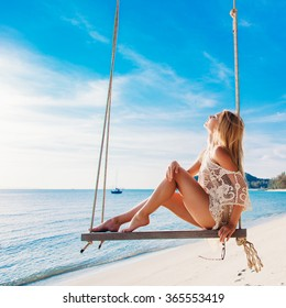 Summer portrait of beautiful stunning blonde woman sitting on swing on the beach on blue sea and green palms background smiling and having fun