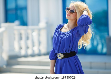 Summer portrait of a beautiful young blonde Caucasian girl with straight hair in blue dress outdoors in the city