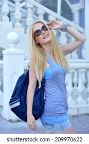 Summer portrait of a beautiful young blonde Caucasian girl with straight hair outdoors in the city
