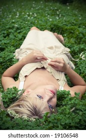 Summer. Portrait of  blonde girl having rest at clover meadow