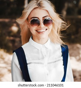 Summer portrait of blonde smiling girl in sunglasses