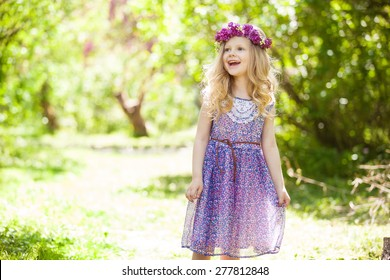 Summer portrait of cute blond girl dressed wreath of lilac on a head in green field.