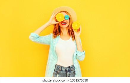 Sommerportrait glückliche lächelnde Frau, die sich in ihren Händen Scheiben Orange hält, die ihre Augen in einem Strohhut auf buntem gelbem Hintergrund versteckt