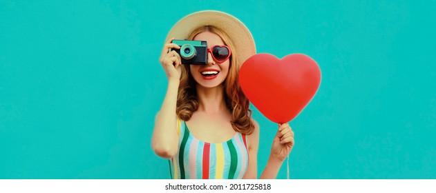 Sommerporträt einer glücklich lächelnden jungen Frau mit Retro-Kamera und rotem, herzförmigen Ballon mit einem Strohhut auf blauem Hintergrund