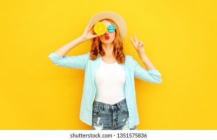 Summer portrait happy woman holding in her hands slices of orange hiding her eyes, sending sweet air kiss in straw hat, shorts on colorful yellow background