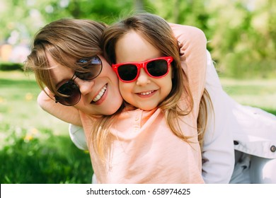 Summer. Portrait of mother with daughter having fun. Woman and girl child kid in sunglasses.
