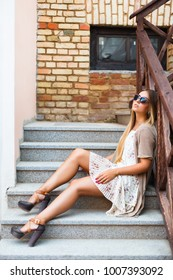 Summer portrait of pretty stylish sensual blonde woman having fun on the street fashion style closeup sitting on stairs in cafe