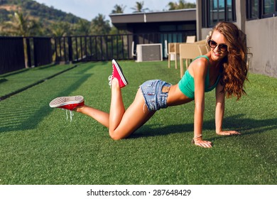 Summer portrait of sexy hipster woman, having fun on the roof at tropical island, wearing crop top denim micro shorts and sunglasses, brunette fluffy hairs, urban background.