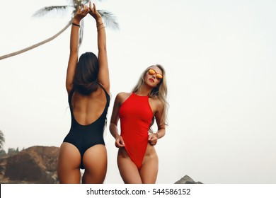 summer Portrait of two glamour friends on the beach looking at camera laughing.girls in similar bikini