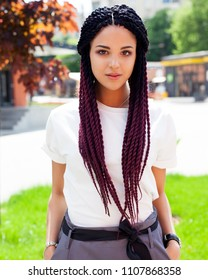 Summer portrait. Young beautiful girl posing on a sunny afternoon in a cool outfit. African braids. Outdoor.
