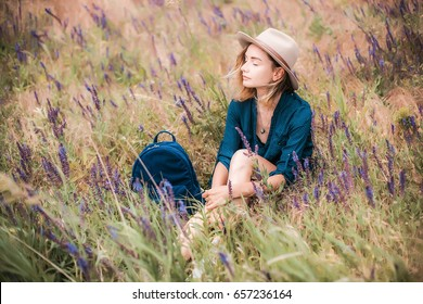 Summer portrait of young hipster woman sitting in a grass on sunny day.young slim beautiful woman with blue bag,bohemian outfit,indie style,summer vacation,fun, positive mood,romantic,woman in hat