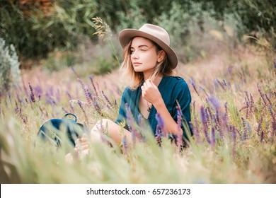 Retrato de verão de jovem mulher hipster sentada em uma grama no dia ensolarado.jovem mulher magra bonita, roupa boêmia, estilo indie, férias de verão, ensolarado, se divertindo, humor positivo, romântico, mulher de chapéu