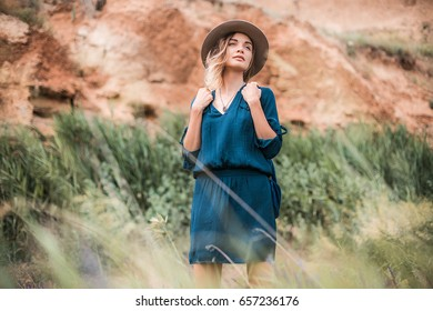 Summer portrait of young hipster woman standing in a grass on sunny day.young slim beautiful woman,bohemian outfit,indie style, summer vacation,sunny,having fun, positive mood,romantic,woman in hat