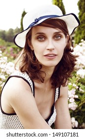 Summer portrait of young pretty woman in white hat